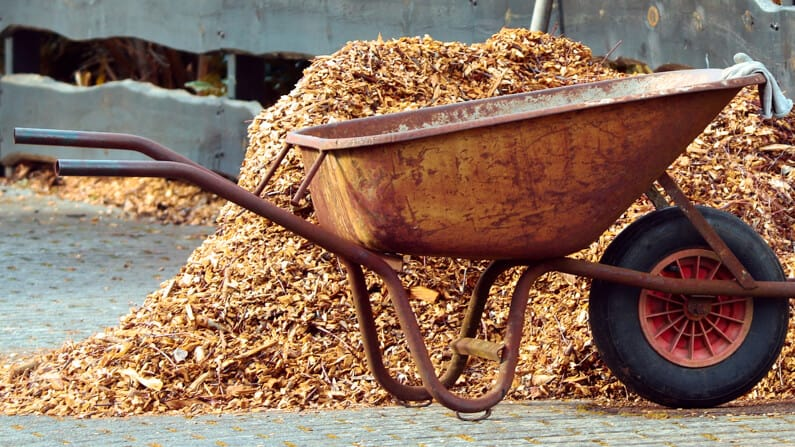 organic mulch, wood chips next to a wheelbarrow